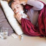 Eine junge Frau liegt mit einer Erkältung oder Grippe auf dem Sofa. Neben ihr stehen diverse Medikamente