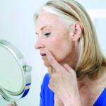Eine Frau sieht sich ihr Gesicht im Spiegel an. Im Winter kommt es auf eine besondere Hautpflege an.