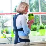 Eine Frau trägt eine Rückenorthese und lindert somit die Schmerzen der Osteoporose.