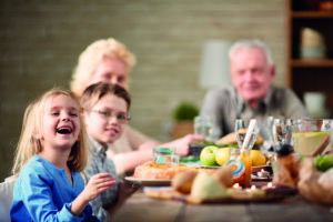 Ein älteres Paar sitzt gemeinsam mit ihren Enkelkindern zum essen am Tisch. Mangelernährung stellt für die beiden kein Problem mehr dar.