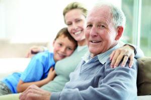 Ein älterer Mann sitzt glücklich mit seinen Familienangehörigen auf dem Sofa. Mangelernährung ist für ihn kein Problem mehr.