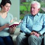 Eine junge Frau liest einem älteren Mann im Rollstuhl aus einem Buch vor. (Eltern werden alt)