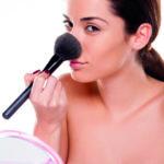 Eine Frau pudert sich ihre Nase mit einem Pinsel. (gestresste Haut)