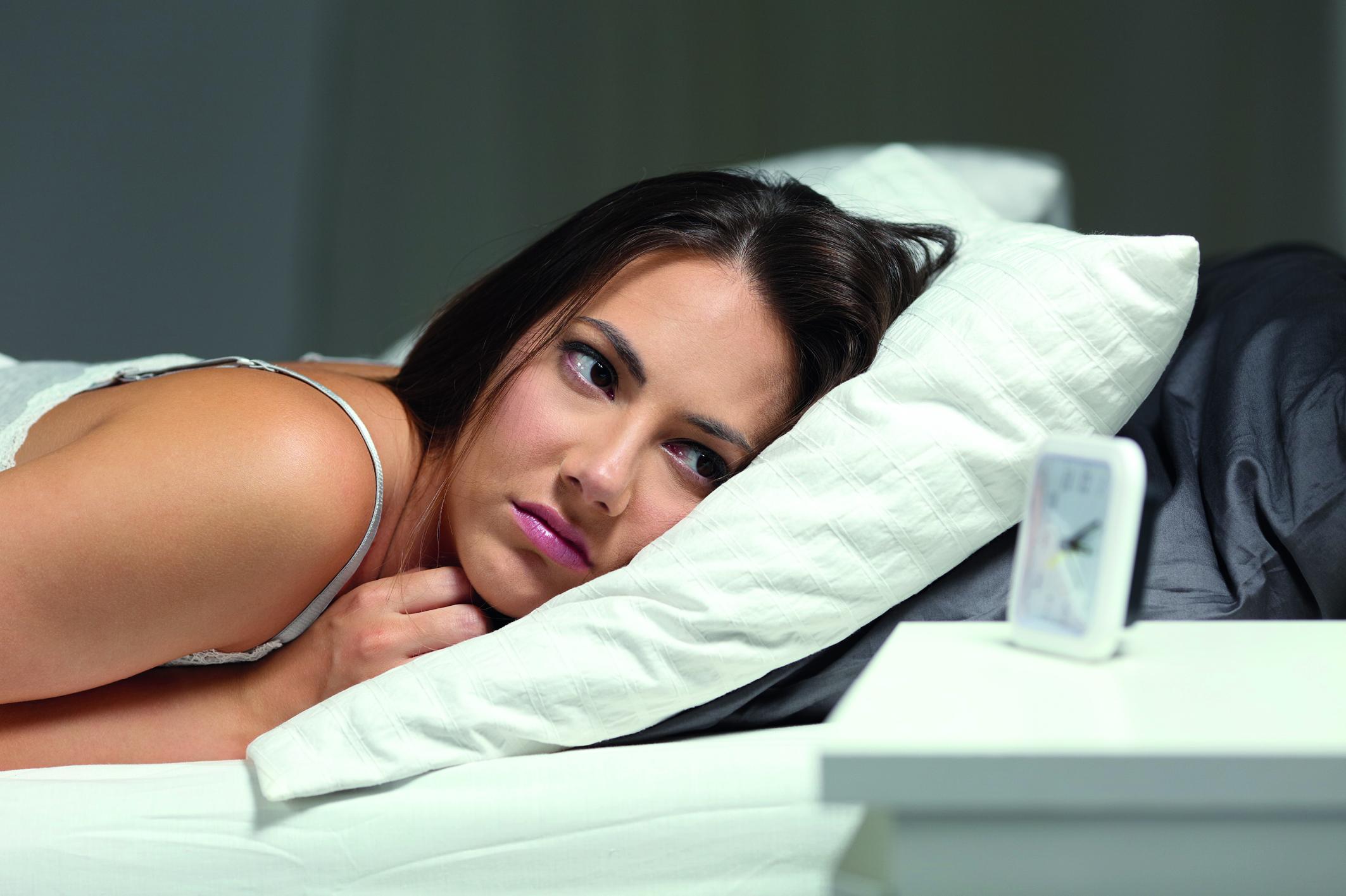 Eine Frau liegt wach im Bett und schaut auf den Wecker (Schlafstörungen).