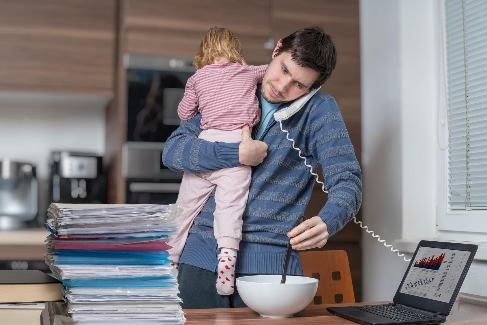 Um ständige Erreichbarkeit zu gewährleisten, arbeitet ein junger Mann während er gleichzeitig Essen zubereitet und ein Kind betreut.