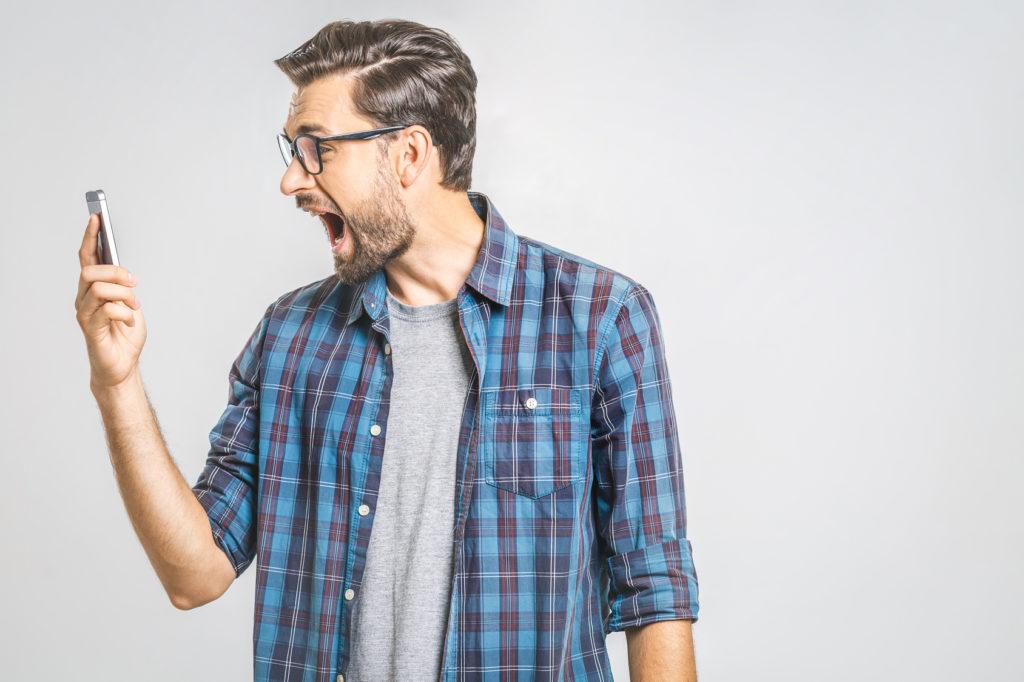 Ein junger Mann brüllt sein Smartphone an. (Ständige Erreichbarkeit)