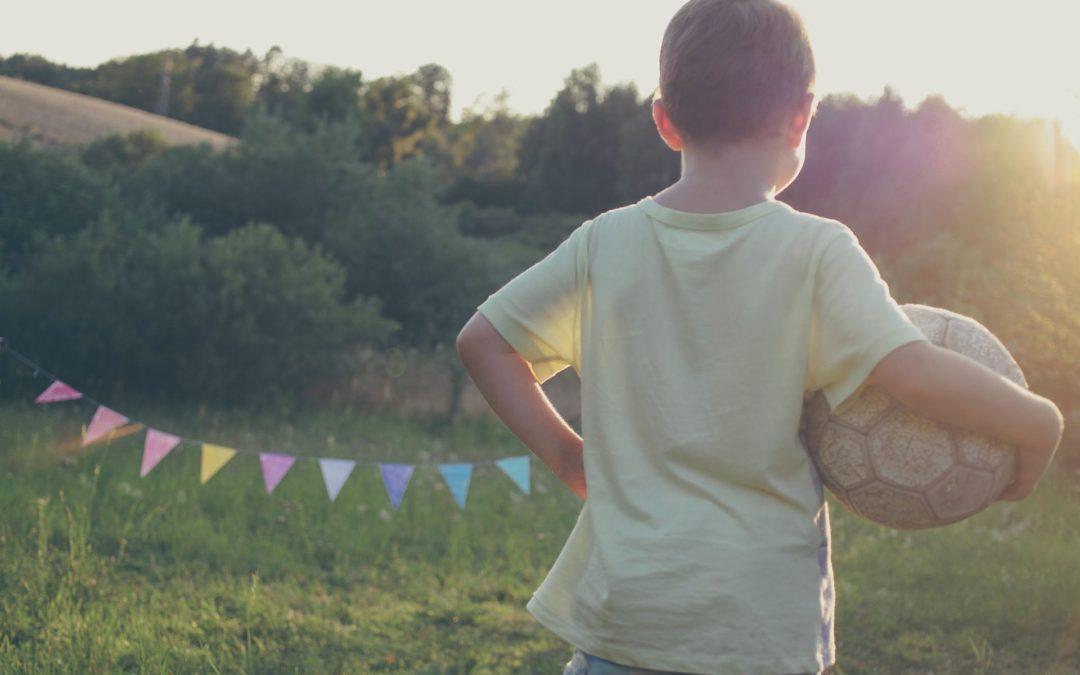 Ein Junge trägt einen Fußball im Freien (Sport für Kinder)