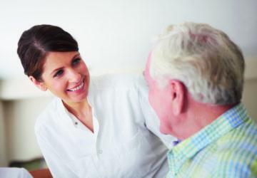 Eine Frau in einem weißen Kittel lächelt einen älteren Mann an (Mangelernährung).