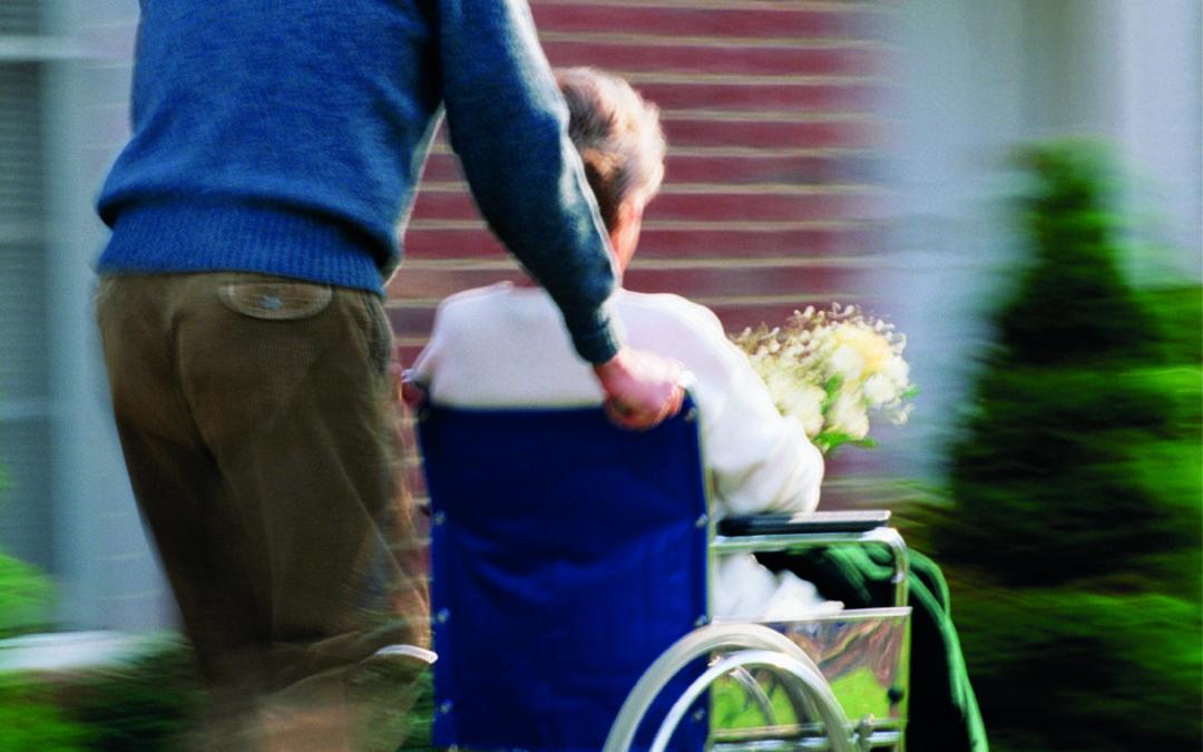 Ein Mann schiebt eine ältere Dame im Rollstuhl