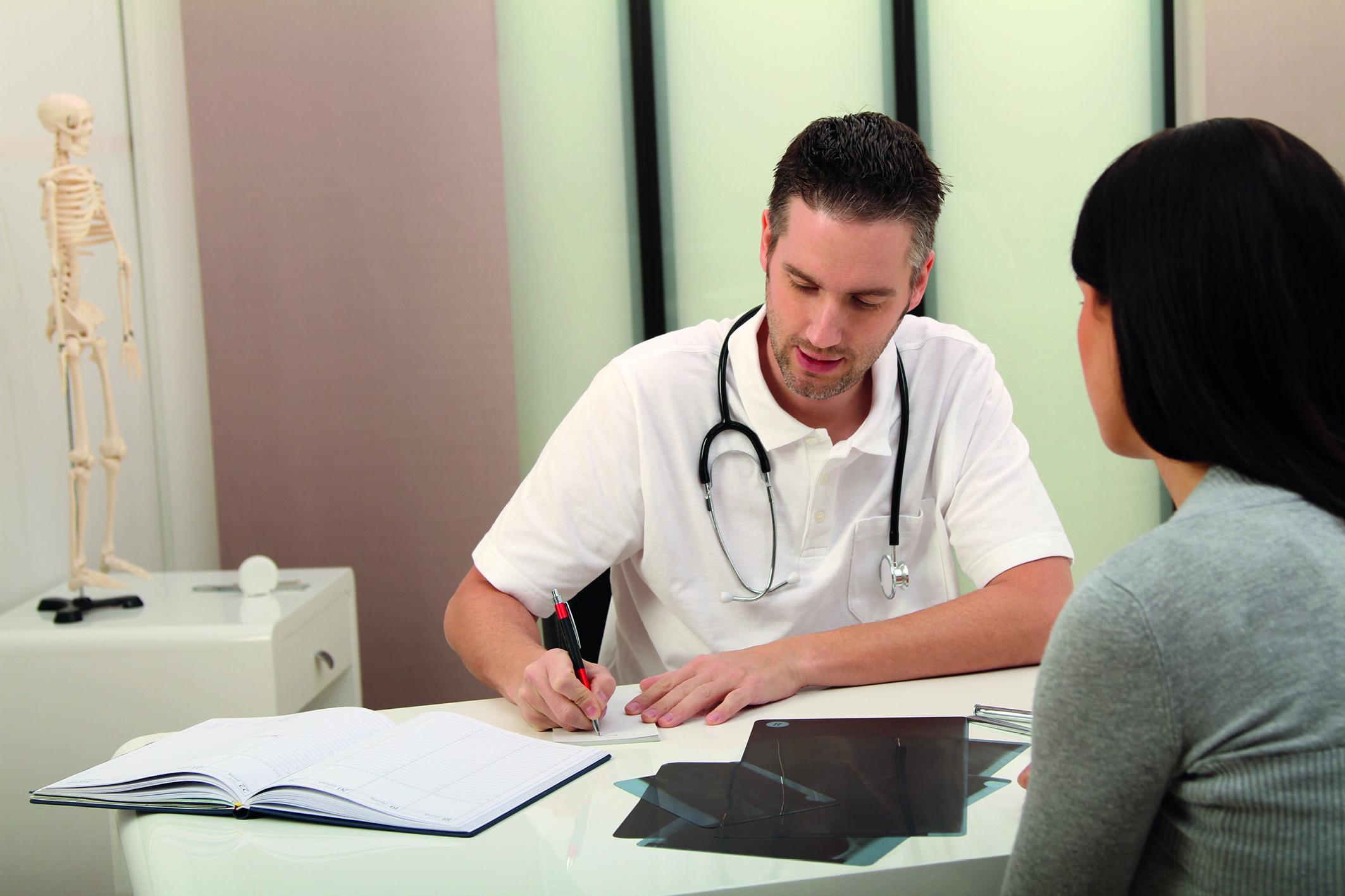 Ein Arzt und eine Patienten sitzen sich gegenüber, der Arzt notiert sich etwas (Berufsunfähigkeit).