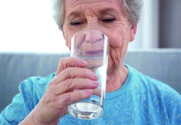 Eine ältere Frau trinkt aus einem großen Glas.