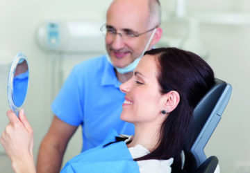 Zahnarzt und Patientin: eine Frau sitzt lächelnd auf einer Behandlungsliege und schaut in einen Handspiegel (hohe Zahnarztrechnungen vermeiden).
