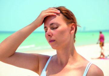 Krank im Auslandsurlaub: Eine Frau steht mit geschlossenen Augen am Strand und hat eine Hand auf die Stirn gelegt.