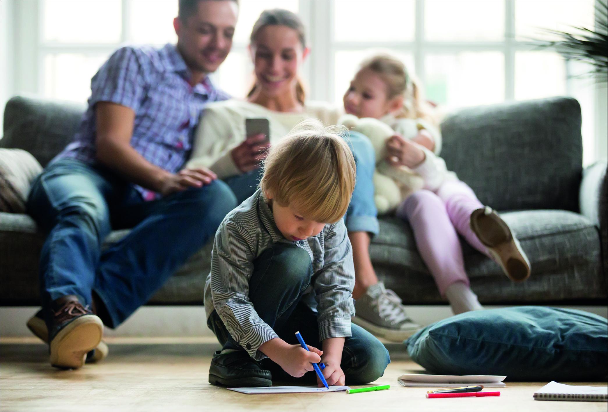 Eltern sitzen mit Tochter auf der Couch, kleiner Junge malt auf dem Fußboden sitzend.