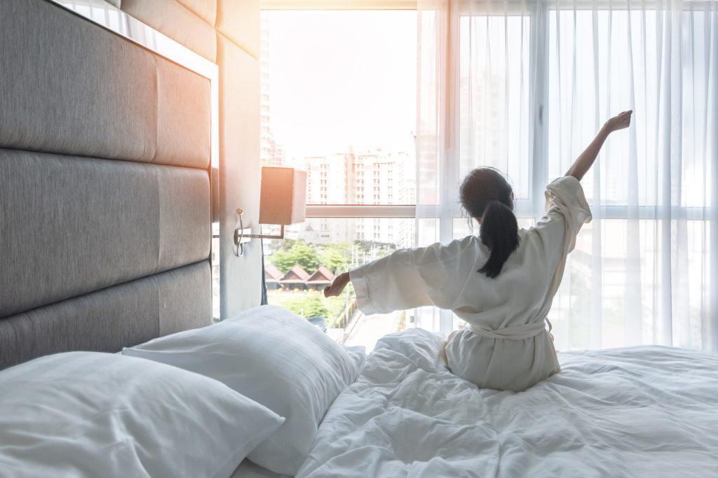 Starkes Immunsystem: eine Frau sitzt mit dem Blick in Richtung Fenster auf der Bettkante und streckt sich.