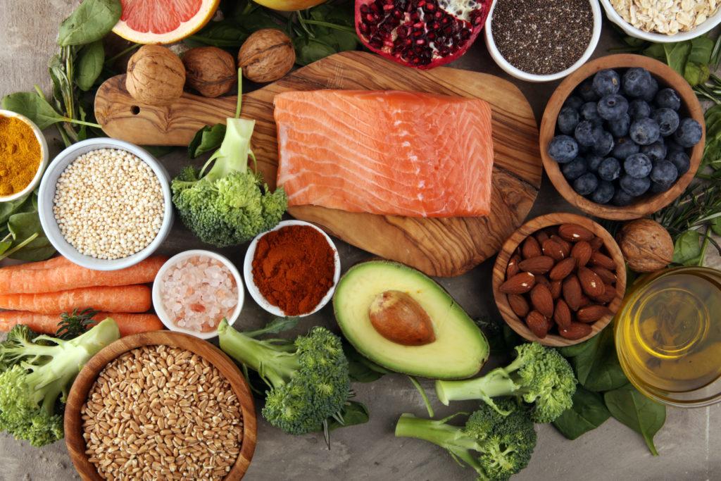 Immunsystem stärken: Fisch, buntes Gemüse und Obst, Nüsse, Gewürze, Kräuter und Öle nebeneinander