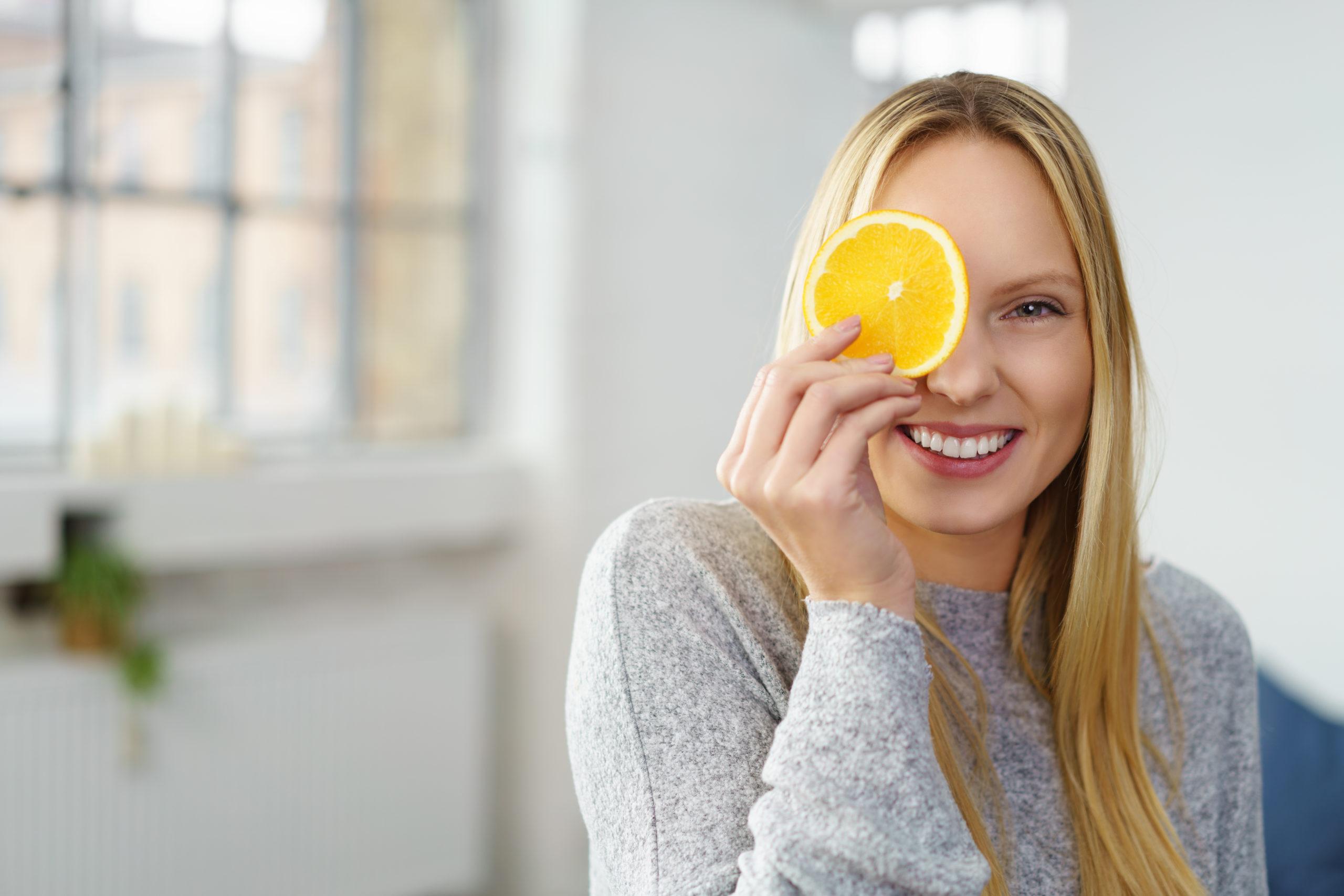 Immunsystem stärken: eine lachende Frau hält sich mit einer Hand eine Orangenscheibe vor ein Auge.
