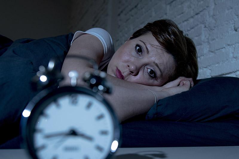 Laute Nachbarn: eine Frau liegt schlaflos im Bett und schaut ihren Wecker an.