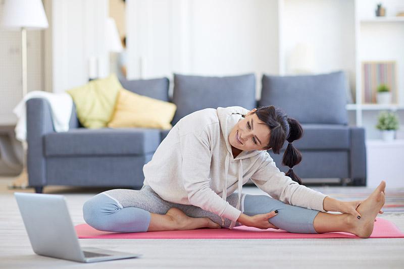 Eine Frau sitzt im Wohnzimmer auf einer Sportmatte und dehnt sich (laute Nachbarn).