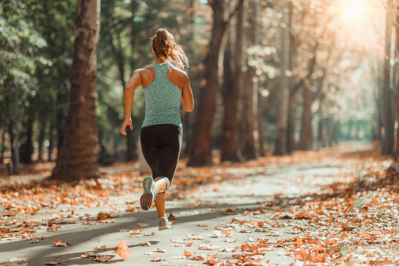 Eine Frau joggt in einem Waldstück bei Sonnenschein (laute Nachbarn).