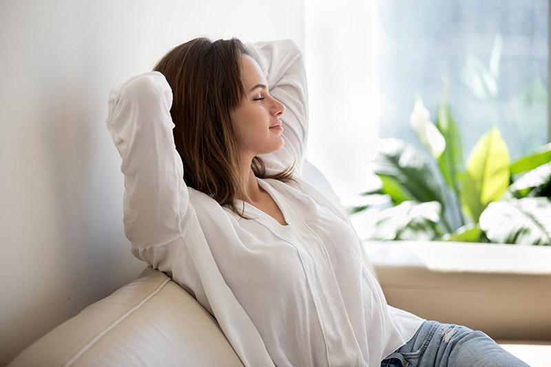 Laute Nachbarn: eine junge Frau sitzt mit geschlossenen Augen auf einem Sofa.