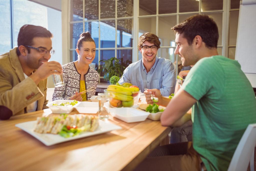Vor dem Powernap: eine Gruppe von Arbeitnehmern sitzen gemeinsam an einem Tisch und essen.