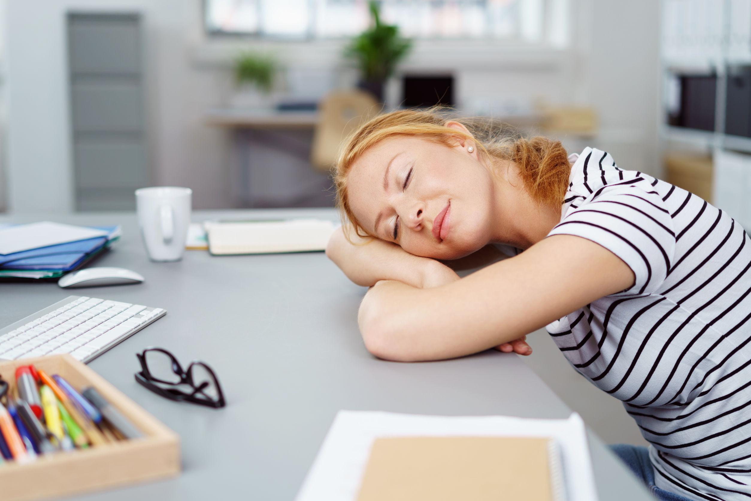 Powernapping: eine junge Frau liegt mit dem Kopf auf dem Schreibtisch und schläft.