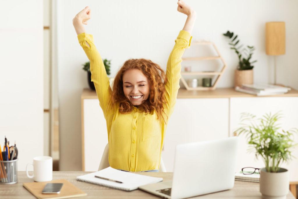 Eine junge Frau streckt sich auf ihrem Bürostuhl (Powernap).