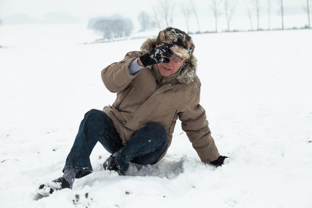Ein älterer Herr ist im Schnee gestürzt – besonders bei Osteoporose ein Verletzungsrisiko.